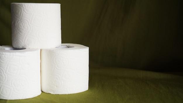 Toilettenpapier ist in krisenzeiten ein muss. geweberollen auf dunkelgrünem hintergrund für exemplar
