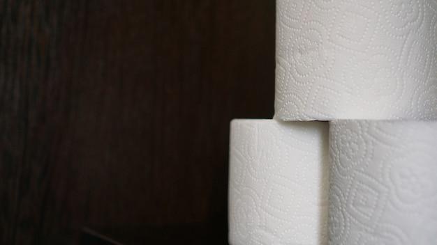 Toilettenpapier ist in krisenzeiten ein muss. geweberollen auf dunklem hintergrund für exemplar