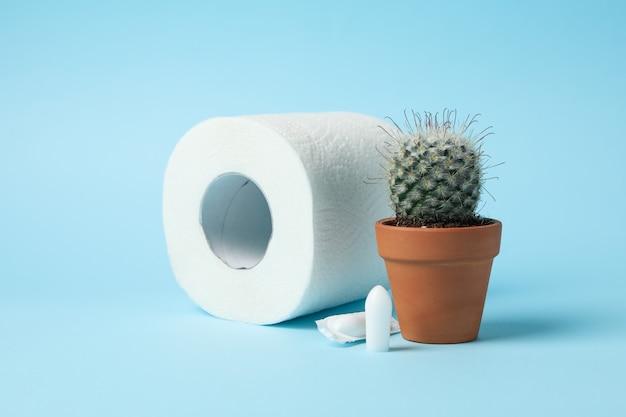 Toilettenpapier, kaktus und kerzen auf blau, nahaufnahme