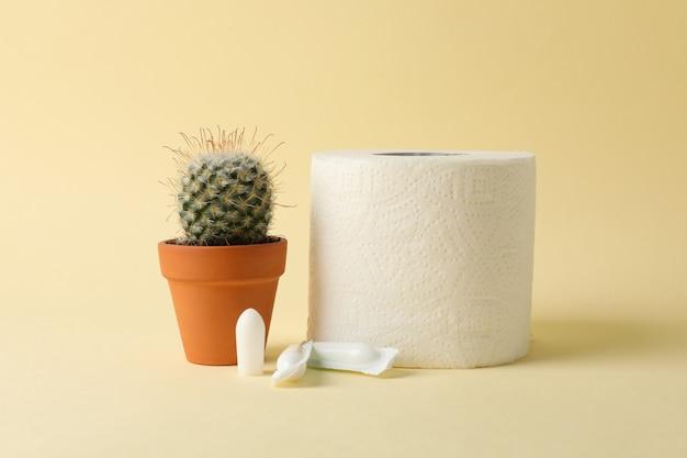 Toilettenpapier, kerzen und kakteen auf beige. hämorrhoiden