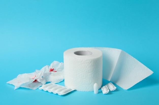 Toilettenpapier, kerzen und papier mit blut auf blau, nahaufnahme