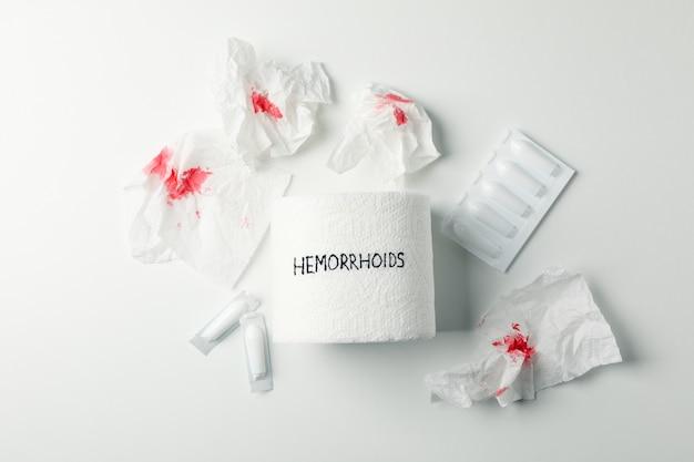 Toilettenpapier mit hämorrhoiden, kerzen und papier mit blut auf weiß, draufsicht