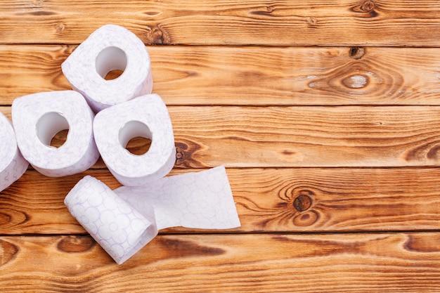Toilettenpapier rollt auf hölzerner draufsicht