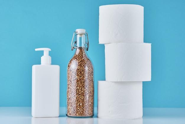 Toilettenpapierrolle, buchweizen und antiseptisches gel mit inschrift stoppen panik auf blauem hintergrund