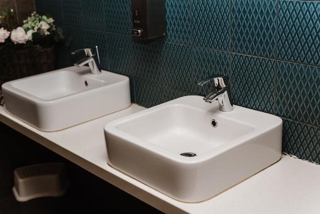 Toilettenwanneninnenraum der öffentlichen toilette mit waschenden händen. nahansicht