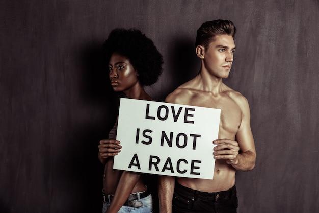 Tolerant sein. schönes nettes paar, das ein zeichen zusammenhält, während es tolerant zueinander ist