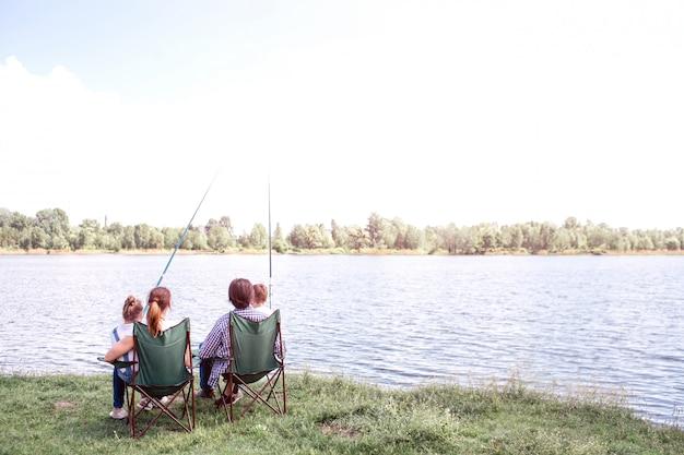 Tolle aussicht auf den großen fluss fließt. da sitzt eine familie am ufer und genießt den moment. sie halten kinder auf dem schoß. kinder halten fischruten in händen.