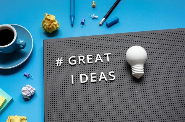 Tolle ideen mit text und glühbirne auf dem schreibtisch arbeitstisch