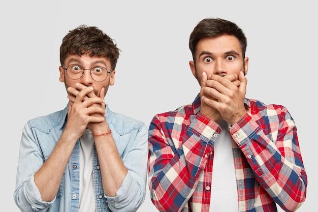 Tolle männer mit ängstlichem gesichtsausdruck, schließen den mund mit den händen, versuchen sprachlos zu sein, erzählen niemandem geheime informationen, isoliert über einer weißen mauer