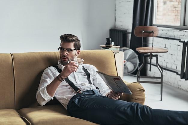 Tolle möglichkeit zum entspannen. stilvoll gekleideter junger mann, der eine zeitung liest und ein glas hält, während er auf dem sofa sitzt