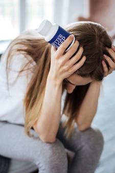Tolle pillen. erschöpfte blonde frau sitzt und schaut auf ihre schlaftabletten