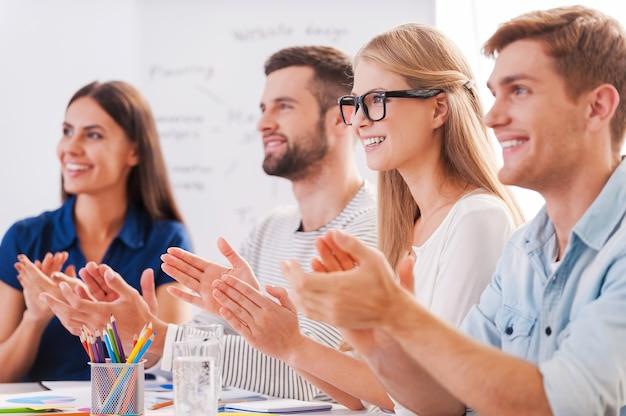 Tolle präsentation! gruppe glücklicher geschäftsleute in eleganter freizeitkleidung, die zusammen am tisch sitzen und jemandem applaudieren