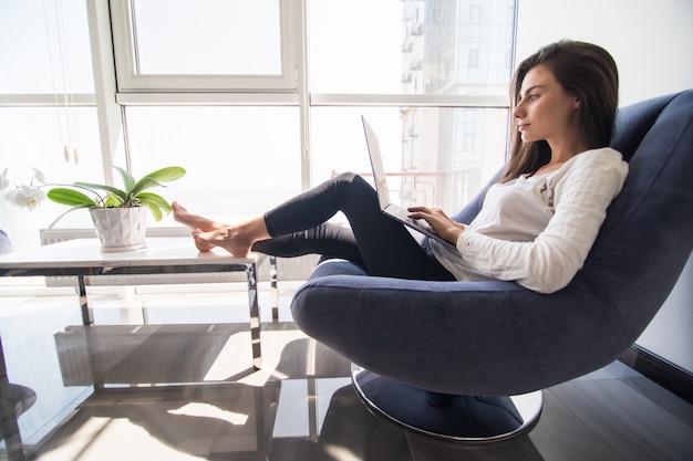 Tolle zeit zu hause. schöne junge lächelnde frau, die am laptop arbeitet, während sie in einem großen bequemen stuhl zu hause sitzt