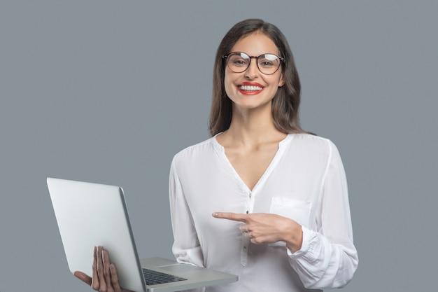 Toller laptop. junge freudige geschäftsfrau mit dem langen dunklen haar, das die brille hält, die laptop zeigt