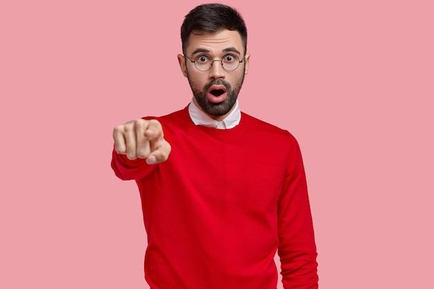 Toller mann mit herausgesprungenen augen, zeigt direkt mit dem zeigefinger, sieht eine erstaunliche szene, hat den atem angehalten, dunkle borsten, isoliert über rosa raum