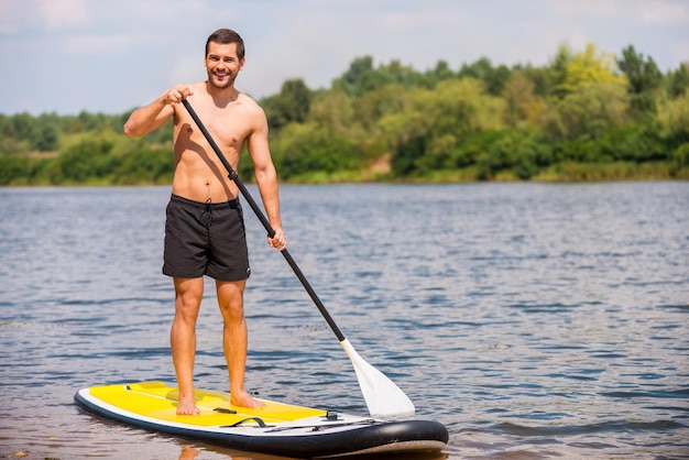 Toller tag zum paddeln. hübscher junger mann, der auf seinem paddleboard surft und lächelt