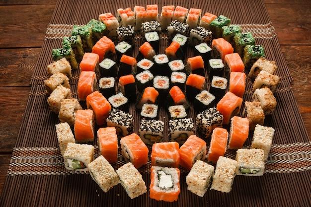 Tolles appetitliches sushi-set, essenskunst. frische bunte runde verzierung von brötchen serviert auf brauner strohmatte, nahaufnahme. japanische meeresfrüchte, restaurantmenüfoto.