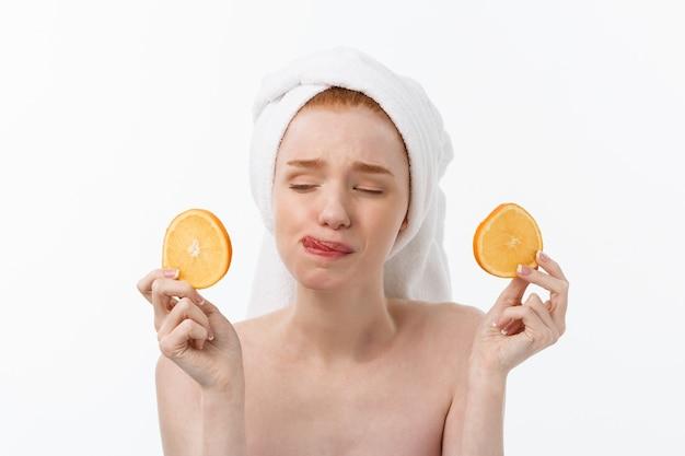 Tolles essen für einen gesunden lebensstil. schöne junge hemdlose frau, die stück orange hält