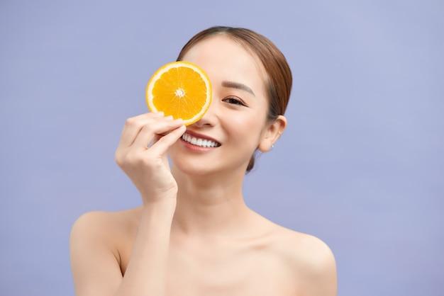 Tolles essen für einen gesunden lebensstil. schöne junge hemdlose frau, die stück orange vor ihrem auge hält, während sie gegen weiße wand steht