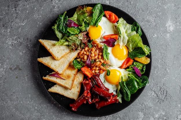 Tolles frühstück mit spiegeleiern, toast, salat und tomaten. in der nähe fotografiert.