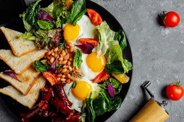 Tolles frühstück mit spiegeleiern, toast, salat und tomaten.