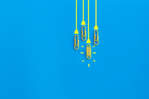 Tolles ideenkonzept mit büroklammer, denken, kreativität, glühbirne auf blauem hintergrund, neues ideenkonzept.