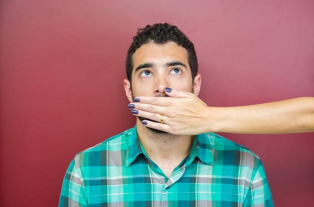 Tolles konzept der weiblichen zensur, mann mit mund von frauenhand bedeckt.