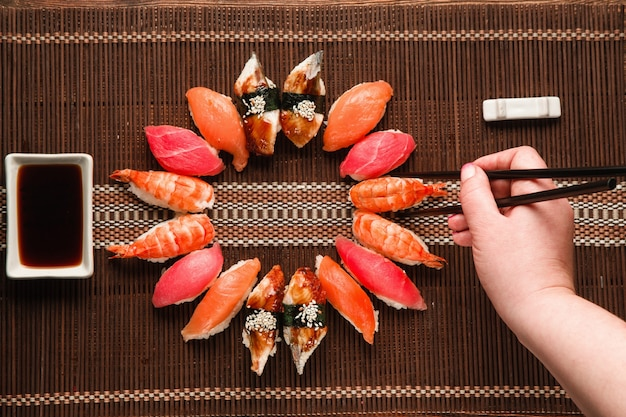 Tolles leckeres set aus buntem nigiri-sushi, serviert in runder form auf brauner strohmatte, flach. unerkennbares handstück mit stäbchen. japanische küche.