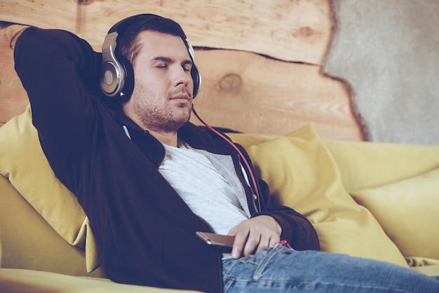 Tolles lied! junger mann mit kopfhörern hält die augen geschlossen, während er zu hause auf der couch sitzt