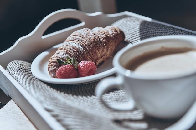 Tolles morgendliches essen. nahaufnahme von croissant, erdbeere und einer tasse kaffee auf dem tablett
