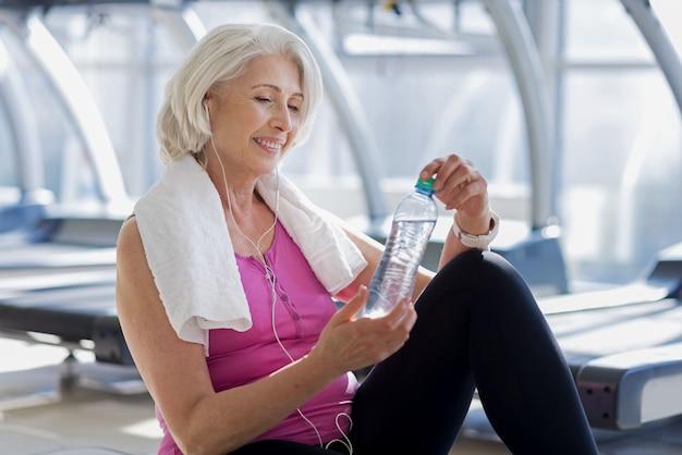 Tolles training. emotionale hübsche ältere frau, die lächelt und eine flasche wasser hält, während auf dem boden in einem fitnessstudio ruht.