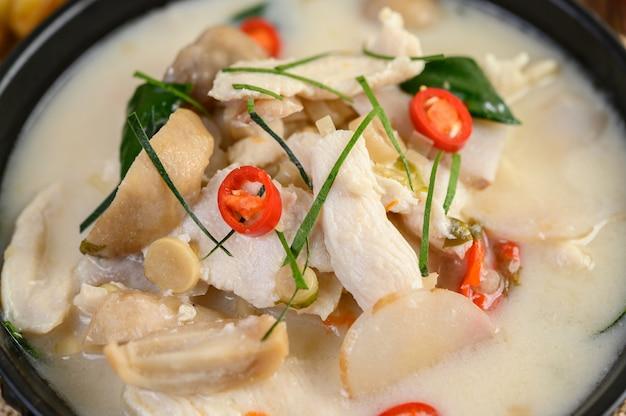 Tom kha kai in einer pfanne mit kaffirlimettenblättern, zitronengras, roten zwiebeln, galangal und chili.