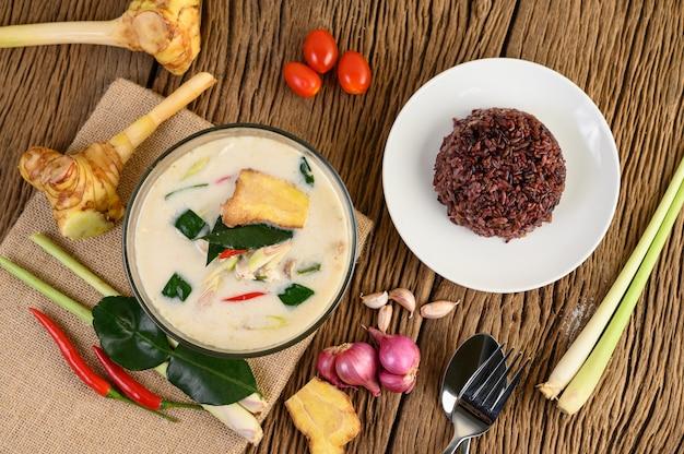 Tom kha kai in einer schüssel mit kaffirlimettenblättern, zitronengras, roten zwiebeln, galangal und chili.