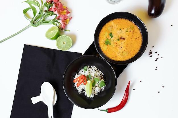Tom kha. würzige würzige asiatische suppe mit auberginen, hühnchen, pilzen, zitronengras, serviert mit reis und koriander.
