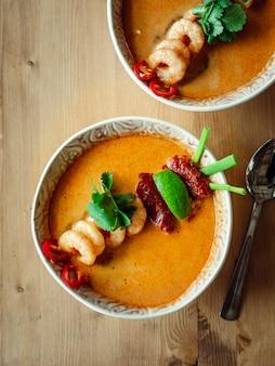 Tom yam kong oder tom yum suppe auf holztisch