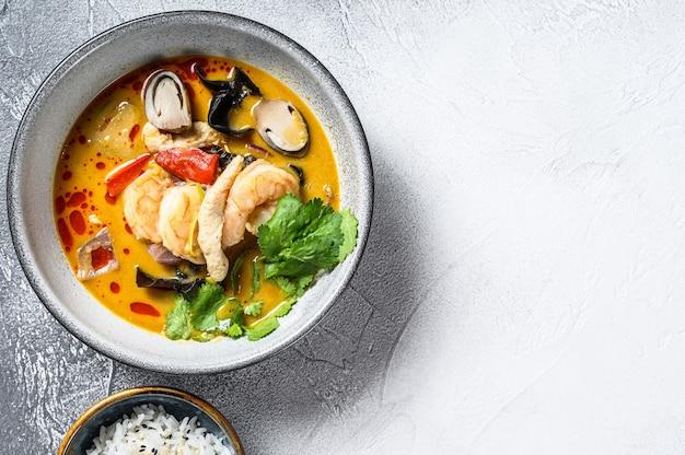 Tom yam kong oder tom yum, würzige klare suppe. tom yam. grauer hintergrund. draufsicht. speicherplatz kopieren