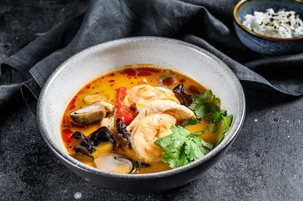Tom yam kong oder tom yum, würzige klare suppe. tom yam. schwarzer hintergrund. draufsicht