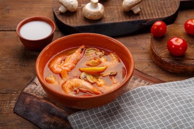 Tom yam suppe mit garnelen in einem teller auf dem tisch auf einer serviette neben einer schüssel kokosmilchpilze und tomaten. horizontales foto