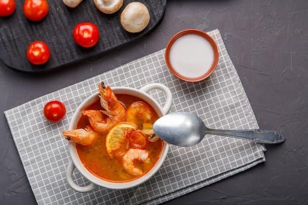 Tom yam suppe mit garnelen in einem teller auf dem tisch auf einer serviette neben pilzen und tomaten. horizontales foto