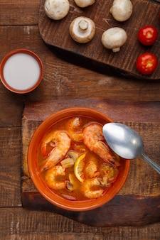 Tom yam suppe mit garnelen in einem teller auf einem holztisch neben einer schüssel mit kokosmilchpilzen und tomaten. vertikales foto