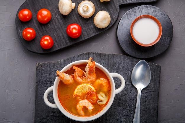 Tom yam suppe mit garnelen in einer terrine auf einem konkreten hintergrund neben einer schüssel mit kokosmilchtomaten und pilzen auf einem holzständer.