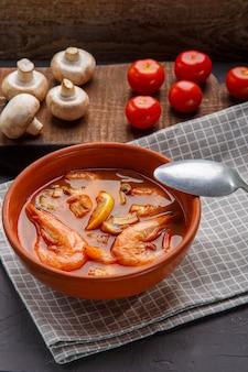 Tom yam suppe mit garnelen in einer terrine auf einem konkreten hintergrund neben einer schüssel mit kokosmilchtomaten und pilzen vertikales foto.