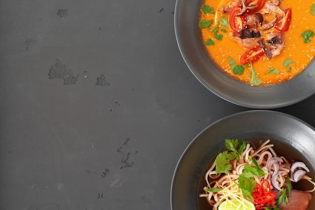 Tom yam suppe und ramen suppe in schalen auf grauer oberfläche