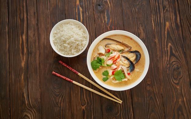 Tom yam würzige thailändische suppe mit garnelen, meeresfrüchten, kokosmilch und chili-pfeffer in weißer schüssel mit reis und stäbchen über hölzerner textur tischoberansicht flache lage, kopieren raum asiatisches nahrungsmittelkonzept