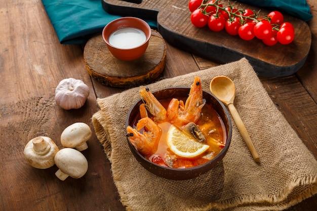 Tom yamsuppe mit garnelen und kokosmilch auf dem tisch auf einer leinenserviette neben gemüse und einem löffel. horizontales foto