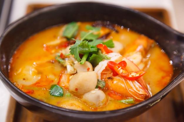 Tom yum goong (tom yum kung), traditioneller thailändischer saurer und würziger tiger prawn soup auf hölzernem t