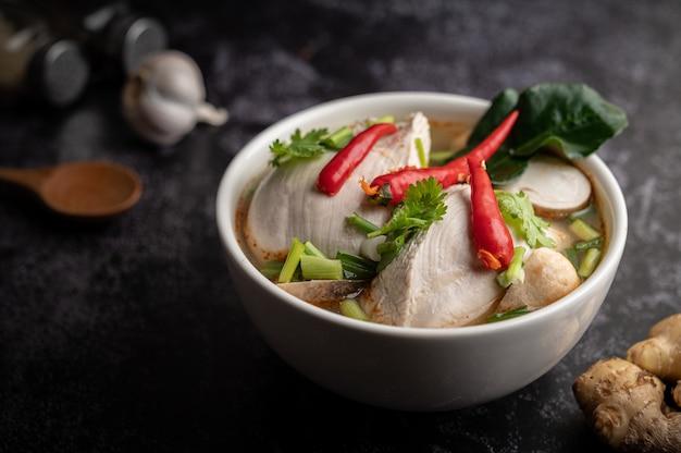 Tom yum huhn mit chili, koriander, getrocknetem chili, kaffirlimettenblättern, pilzen und zitronengras in einer schüssel