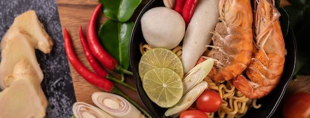 Tom yum kung in einer schüssel mit tomaten-, chili-, zitronengras-, knoblauch-, zitronen- und kaffirlimettenblättern