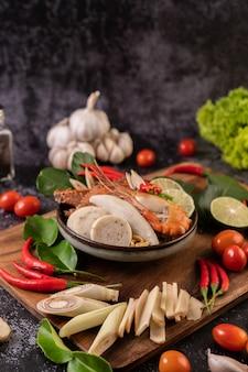 Tom yum mit garnelen und krabben mit limetten-, chili-, tomaten-, knoblauch-, zitronengras- und kaffirlimettenblättern. selektiver fokus.