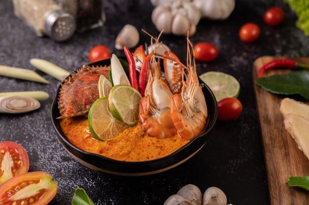 Tom yum mit garnelen und krabben mit limetten-, chili-, tomaten-, knoblauch-, zitronengras- und kaffirlimettenblättern.